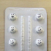 rising: blister-pack medication, with :) drawn onto the plastic above the pills (the cadre: happy pills)