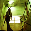 0jack: Greenish shot of a stairway, a woman's form with antlered head and shotgun in hand descending. (Deer Hunter coming.)