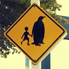 phoenix64: traffic sign with a person holding the hand of a giant penguin (penguin crossing)