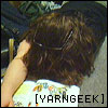 "yarngeek: yarngeek on the floor, hair done Cousin IT style. German picture book is flat on the floor. Text says ""[yarngeek]."" (tired)"