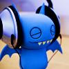 snowcipher: bat figurine wearing headphones (batmusic)
