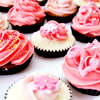 panda: photo of pink cupcakes with decorative frosting (food: om nom nom nom)