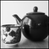 calissa: A black and white photo of a large, dark teapot and a small Chinese teacup with a fish painted on the side (Tea)