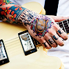 alwayswondered: A man's heavily tattooed hand holding a guitar; the letters 'TRUE' are visible on his fingers. (who who who does it better than we do)