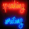 lightreads: the word speaking in handwriting-like red neon above the word writing in handwriting-like blue neon; (speaking writing)