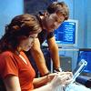 skieswideopen: John Sheppard & Elizabeth Weir leaning over a desk (SG: John & Elizabeth)