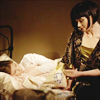 metatxt: miss phryne fisher sits at the edge of the bed, gazing at jane tucked in bed (mfmm: miss fisher and her ward jane)