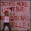 "gavagai: A woman in front of a wall painted with ""Jedes Herz ist eine revolutionäre Zelle"" [Every heart is a revolutionary cell] (jedes herz ist eine revolutionaere zelle)"