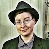 rosefox: A white genderqueer person in a blazer, striped shirt, earrings, and fedora. (suits)