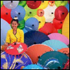 thefourthvine: Person surrounded by umbrellas in rainbow colors.  (Happy umbrella)