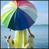 thefourthvine: A woman at the beach with two dogs and a rainbow umbrella. (Umbrella rainbow)