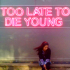 "kianan: a girl sitting under a neon sign that reads ""TOO LATE TO / DIE YOUNG"" (too late to die young)"