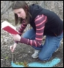 unfavorableinstigation: Nita Callahan kneeling in the woods, drawing a glowing blue diagram on the ground while reading from a book. (Drawing a Spell Diagram)