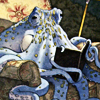 alex_beecroft: A blue octopus in an armchair, reading a book (Octopus)