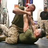 hecu_marine: Two US Marines, one on his back on the ground with his hands on the other's throat as the one on top tries to punch him (cqc)