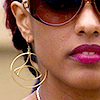 st_aurafina: woman's face close up, she has big hoop earrings and sunglasses (sens8: amanita)