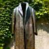 logopraxis: Photo of a human-sized bronze statue of a long trenchcoat, empty and standing alone. (empty)