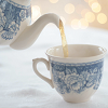 rhi: A white teapot with bluework pouring hot tea into a matching teacup. (teapot)