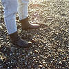 rosefox: My feet on a pebbly beach. (travel, legs, boots, feet, potential)