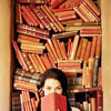 jamethiel: A woman sits in front of a bookshelf, hiding the lower half of her face with an open book (Reading)