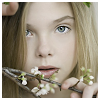 softness: young girl with blue eyes peeking around a flowering branch (peeking from dreams)