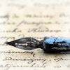 pensnest: fountain pen nib lying across sheet of writing (pen)