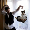 "nightmachinery: Man gesturing with hands above head in a ""doing magic"" pose, with a tuxedo cat hanging in the air as if levitating. (Magnificent - Cat)"