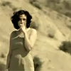 trialia: A curvy, dark-haired woman in a cream dress, standing in a cream-toned, hilly desert landscape with a hand to her mouth. (misc] let me live)