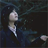 avia: A girl looking up at a dark sky and snow fall with hand holding out to catch snow. (snow falls)