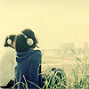 avia: Girl and boy couple, wearing headphones. The boy is looking at her but the girl is staring into the sky. (staring into world)