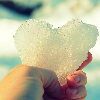avia: A hand holding a heart made of snow/ice. (snow glass apples)