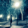 mortalcity: A girl standing under a streetlight in a snowy park. (BW | they say you should not wander)