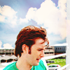 dreamtofbeing: David Tennant in front of an outdoors commercial/airport background. Looking down. (green shirt)