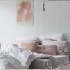 lireavue: A long shot of a queen-sized bed, unmade, with pillows in mild disarray. (very ravelled sleeves)