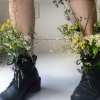 lireavue: A woman in a pair of combat boots with flowers stuck through the laces. (tame the roads that can't be tamed)