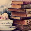 kittydesade: A stack of old, slightly tattered cloth-bound hardbacks next to a porcelain cup of tea on a saucer (quiet day of reading)