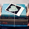 kittydesade: A small stack of books tied together with string, a blue book is the top book with a card with a blue heart on top. (always something to be read)