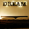 "valerianhouse: Letters spelling ""DREAM"" above a bed's headboard. The letters are wrapped in string lights. (Default)"