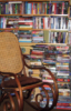 oursin: Books stacked on shelves, piled up on floor, rocking chair in foreground (books)