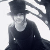 avia: A young girl looking curious, in a top hat. Black and white picture. (girl in a top hat)