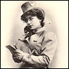 dorinda: From a French postcard of 1902: a woman in hat, coat, cravat, and walking stick writes on a pad of paper. (writer)
