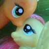 katherine: Applejack and Fluttershy My Little Pony toys, closeup to their faces as they look at each other. (appleshy, otp)
