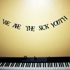"theresistance: A banner reading ""WE ARE THE SICK YOUTH"" hanging over an electric keyboard (Default)"