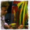 brightknightie: Nick using a large paintbrush and a can of yellow paint on his abstract rendition of his beast (Art)