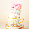 deumion: three multicolored teacups stacked atop each other, topped by a pink rose. (so big~)