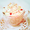 deumion: a delicate teacup, contents obscured by a cone of whipped cream topped with candies. (creamy~)