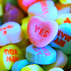 """deumion: a pile of candy hearts, focused on the one that reads """"yes."""" (consensual~)"""