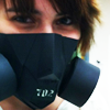 anomily: Close-up of a girl to the left of the picture with short brown hair. She's wearing a black gas mask made out of paper. (gas mask)