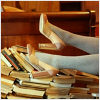 fascination: A photo cropped that it only shows a woman's legs amongst a pile of books. (High-heels and books.)