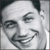 lurrel: a tightly cropped portrait-style photo of Tom Hardy smiling, black and white (Eames' class portrait)